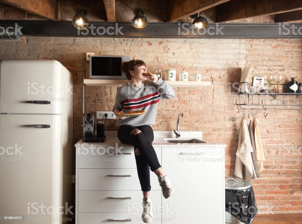 Beautiful girl eating pizza in a modern kitchen Beautiful girl eating pizza in a modern kitchen 16-17 Years Stock Photo