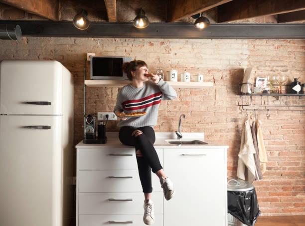 美麗的女孩吃比薩餅在現代廚房 - 即食口糧 個照片及圖片檔