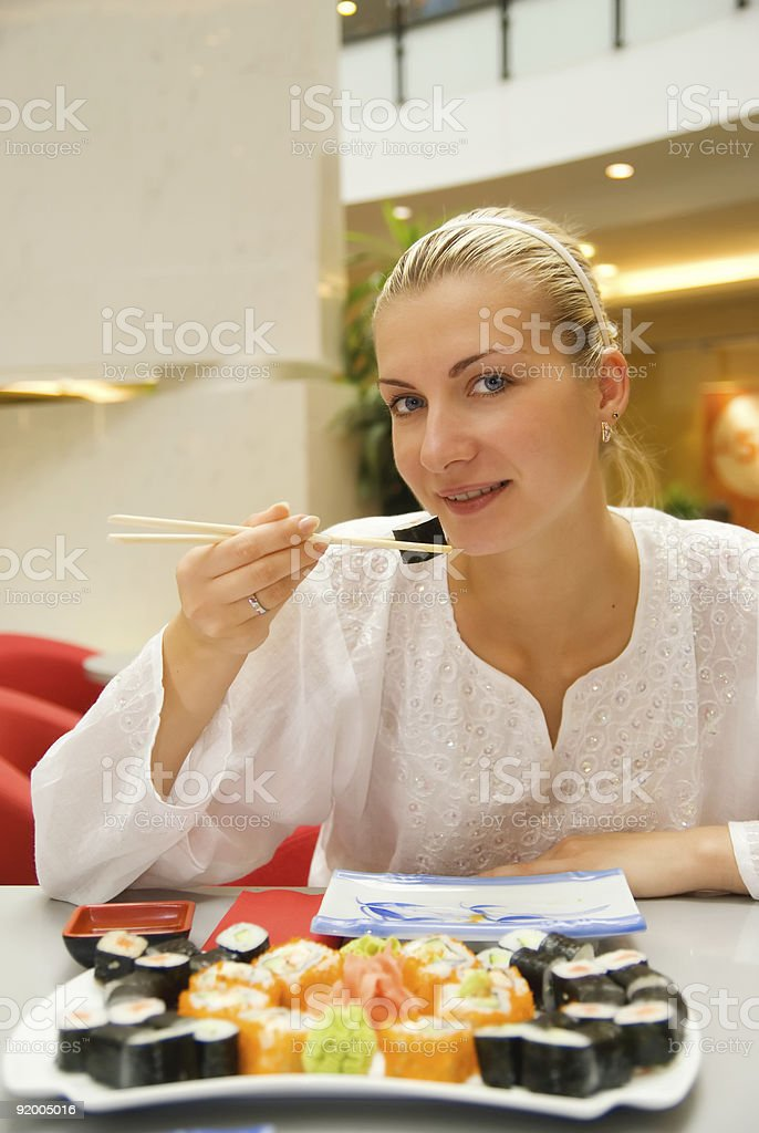 Beautiful girl eats sushi in a restaurant royalty-free stock photo
