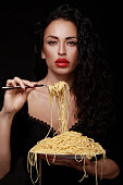 A beautiful girl with red lips eats a fork spaghetti from a full plate. On a black background. Italian cuisine.