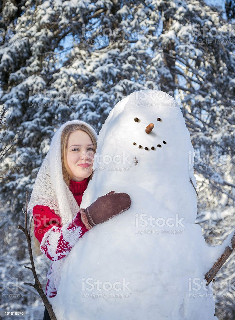 Beautiful girl embracing snowman royalty-free stock photo