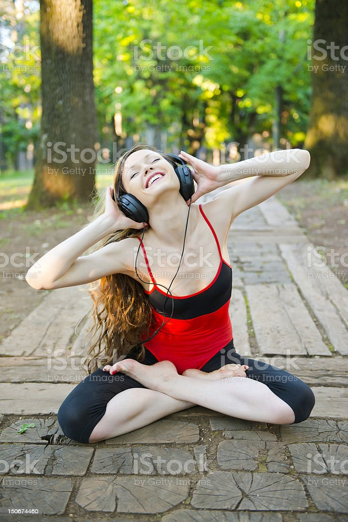 Beautiful girl enjoying fitness and music in the forest stock photo