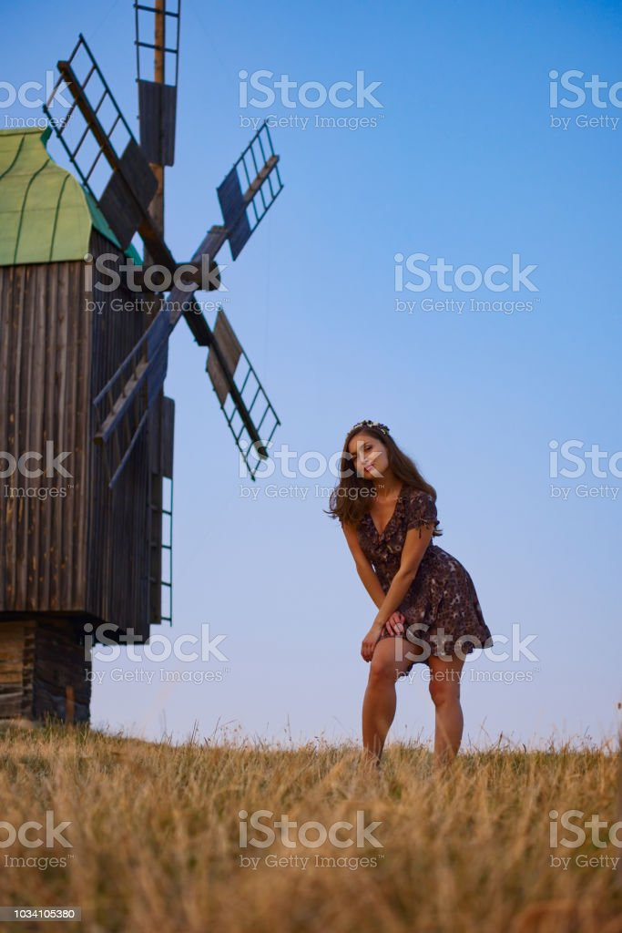 Beautiful girl field and windmill stock photo