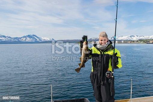 155674939 istock photo Beautiful girl fishing in northern Norway 666798886