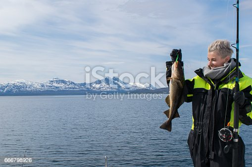 932662672istockphoto Beautiful girl fishing in northern Norway 666798926