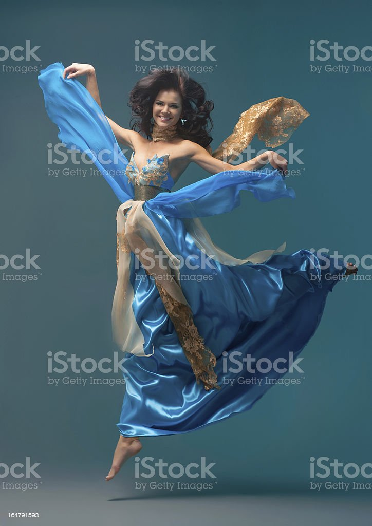 beautiful girl floating in mid-air, blue silk dress royalty-free stock photo
