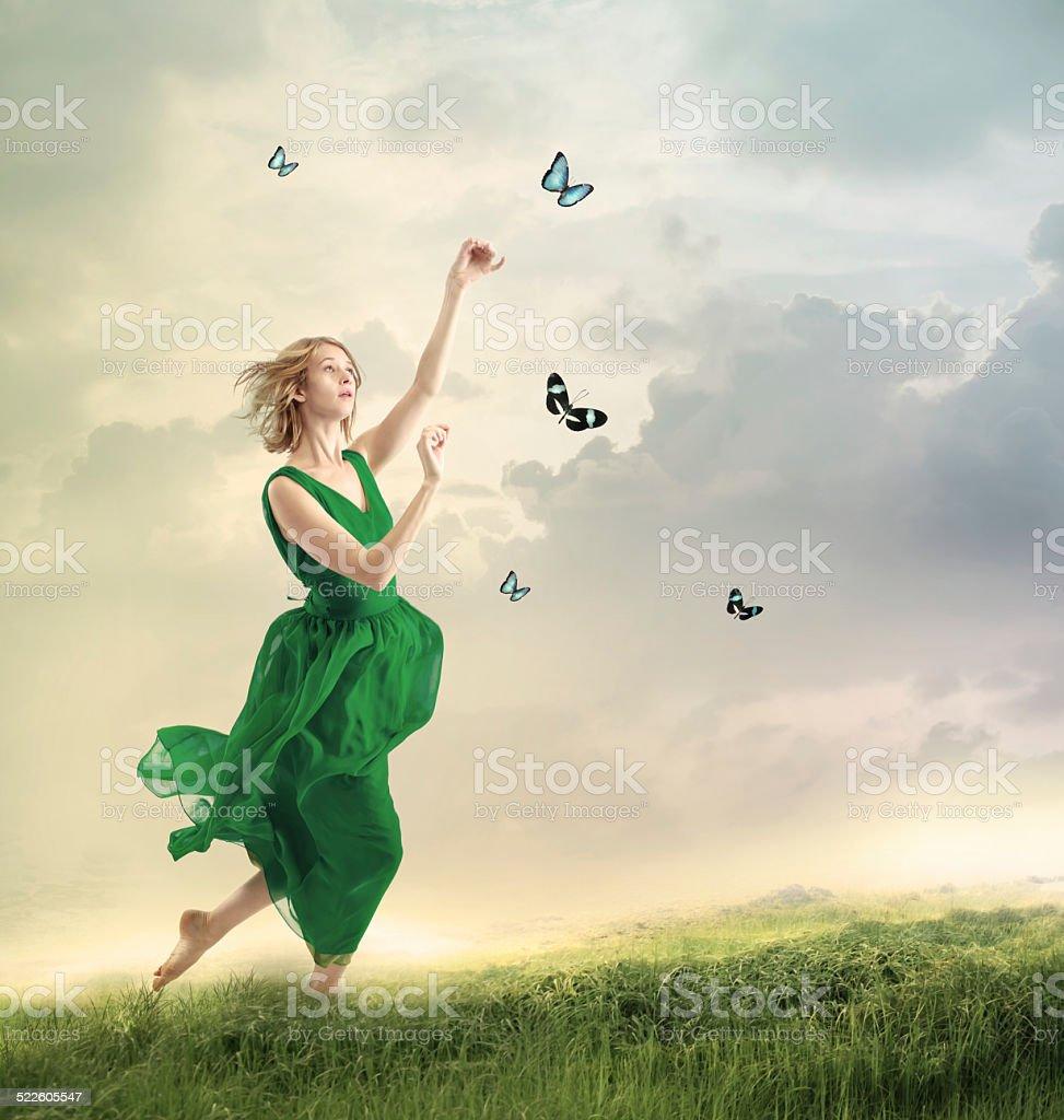 Beautiful girl following butterflies on a mountain stock photo