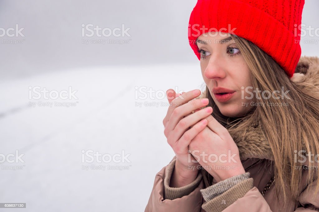 beautiful girl freezing in winter park. Girl warms her hands - ウィンターコートのロイヤリティフリーストックフォト
