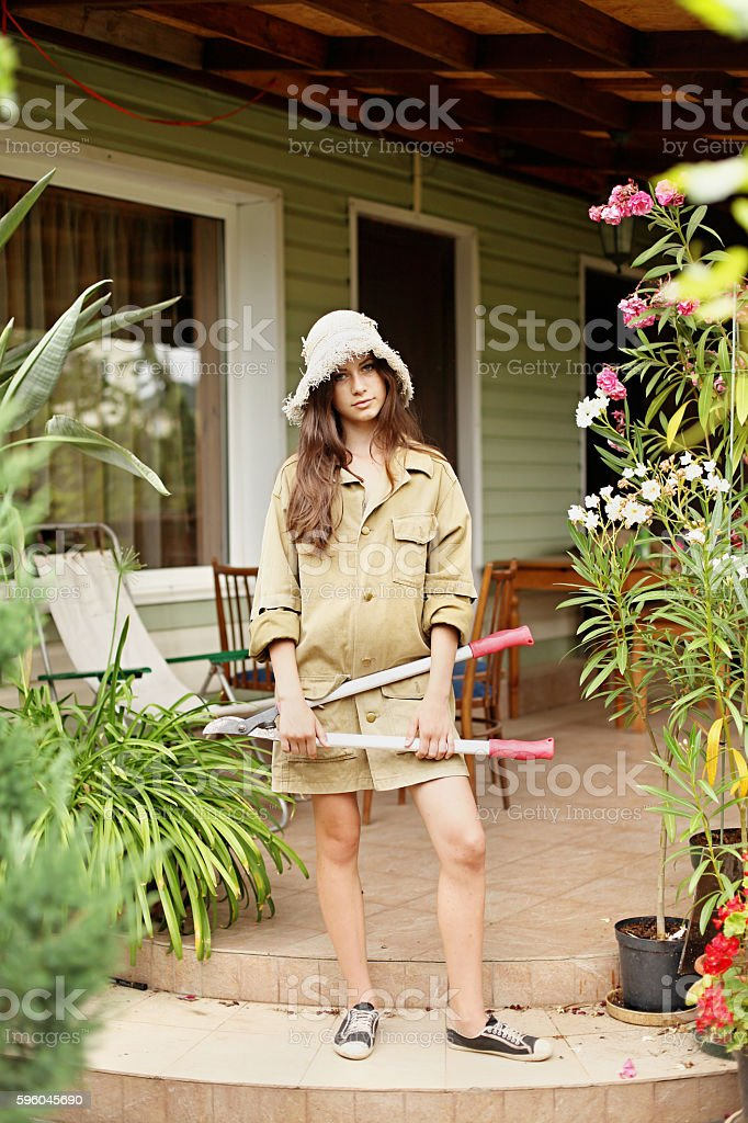 Beautiful girl gardener standing with a large garden scissors royalty-free stock photo