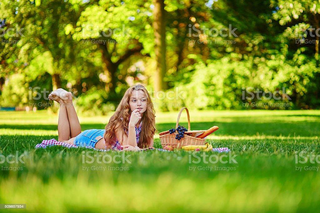 Красивая девушка, имеющих пикник в парке стоковое фото