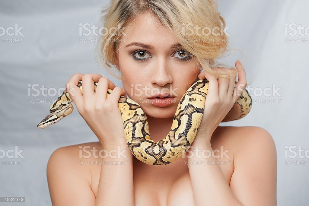 Beautiful girl  holding a python, which wraps around her face stock photo