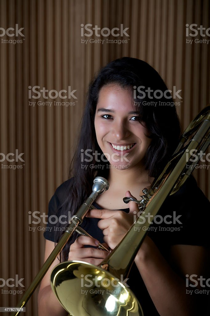 Beautiful girl holding a trombone stock photo