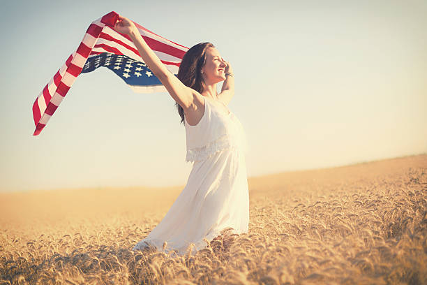 Beautiful girl holding an American flag in the wind stock photo