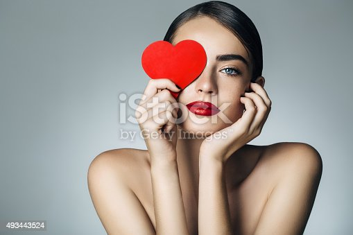 istock Beautiful girl holding artificial heart 493443524