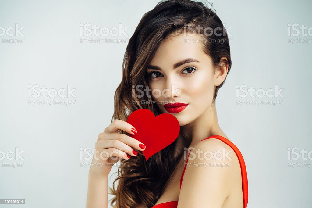 Beautiful girl holding artificial heart stock photo