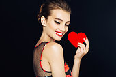 Studio shot of young beautiful woman holding artificial heart. Professional make-up.