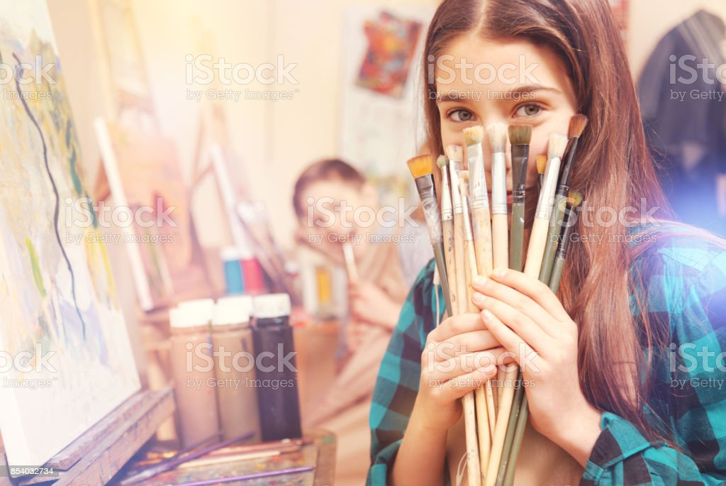 Beautiful girl holding bunch of messy painting brushes stock photo