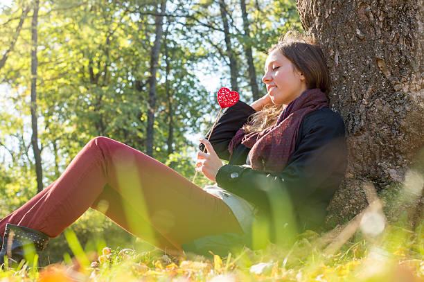 Linda garota segurando símbolo de coração vermelho sobre um palito - foto de acervo