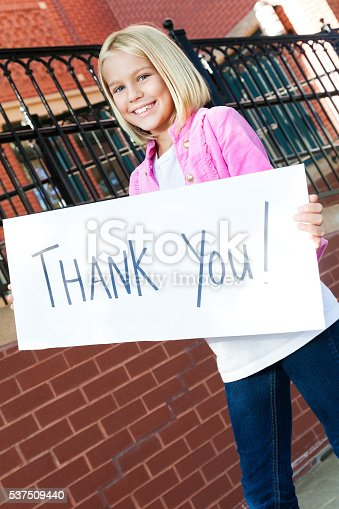 istock Beautiful girl holds 'thank you' sign at school 537509440