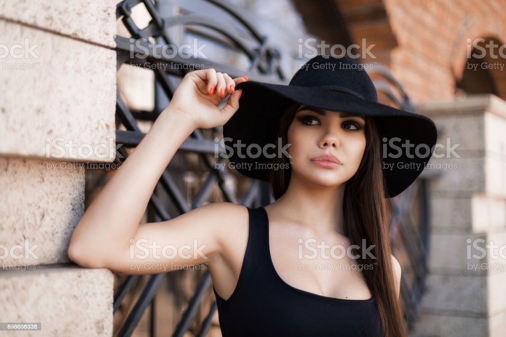 beautiful girl in a black hat walking around the city stock photo
