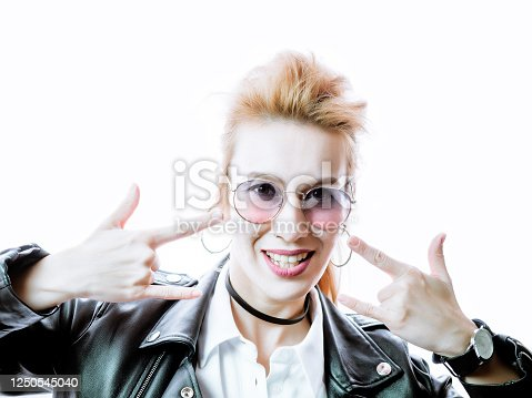 istock A beautiful girl in a black leather jacket and sunglasses shows hands gesture rock on a bright white background. High key 1250545040