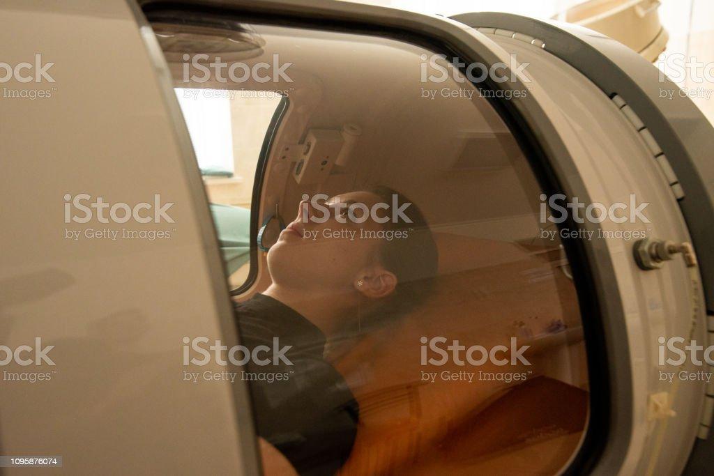 beautiful girl in a black T-shirt lies in a hyperbaric chamber – zdjęcie