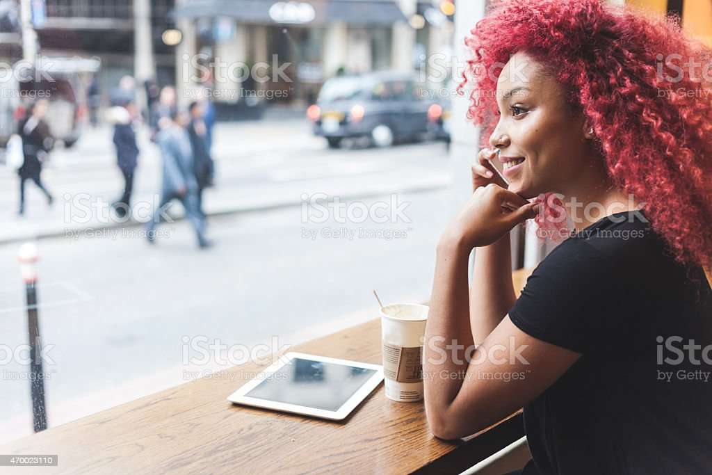 Beautiful girl in a cafe talking on smart phone stock photo
