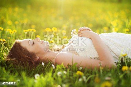 Beautiful girl is relaxing lying on grass in the garden