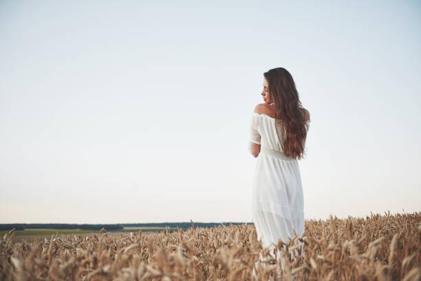 Schönes Mädchen in einem Feld von Weizen in einem weißen Kleid, ein perfektes Bild in den Stil Lifestyle. – Foto