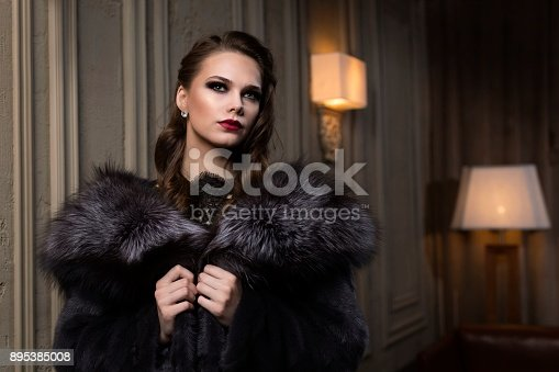 beautiful girl in a fur coat came to a party in a restaurant