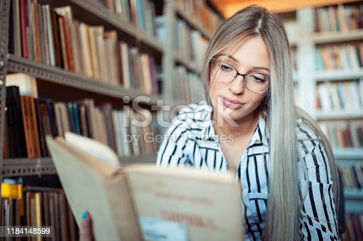 521911045istockphoto Beautiful girl in a library 1184148599
