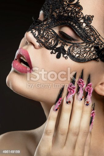 istock Beautiful girl in a mask with long fingernails. 495149159