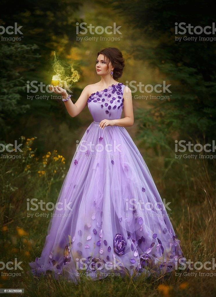 Beautiful girl in a  purple long dress, holding a candle stock photo