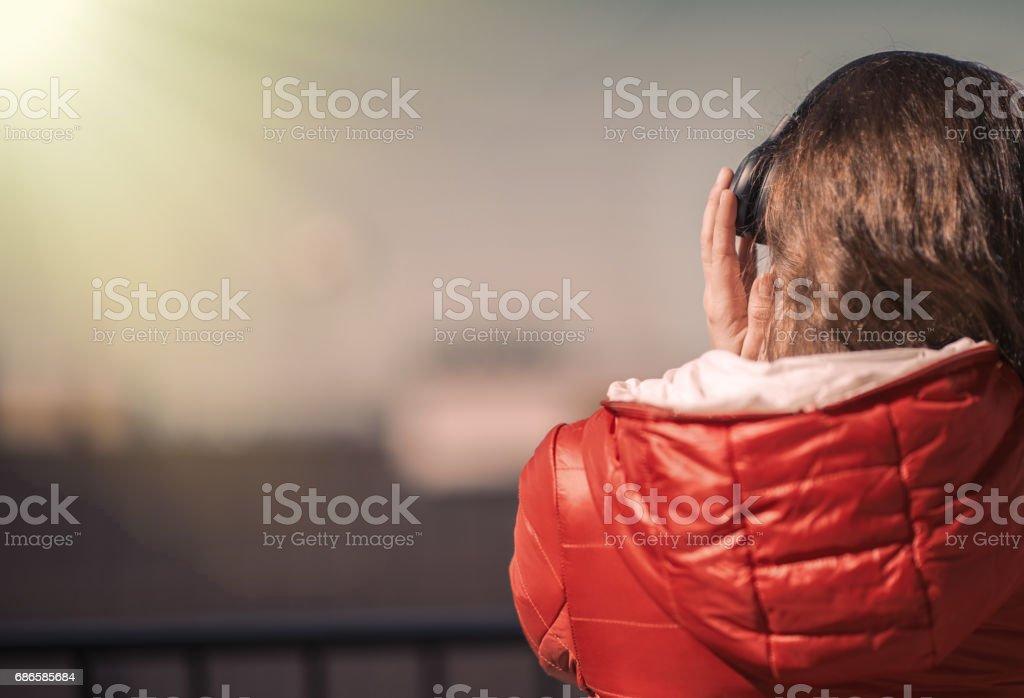 Belle jeune fille dans une veste rouge et un casque. Une fille sur le balcon, écouter de la musique et chante photo libre de droits