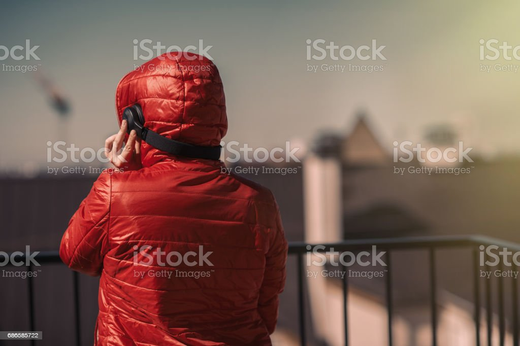 Beautiful girl in a red jacket and headphones. A girl on the balcony listening to music and is singing royalty-free stock photo