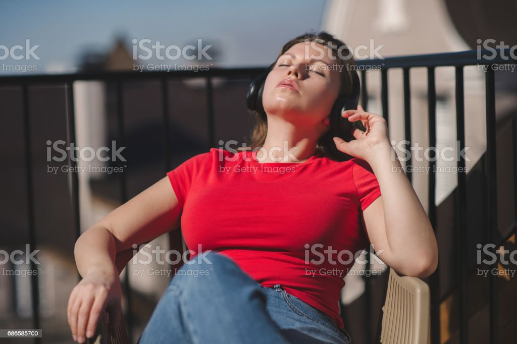 Beautiful girl in a red t-shirt and headphones. A girl on the balcony listening to music and is singing royalty-free stock photo