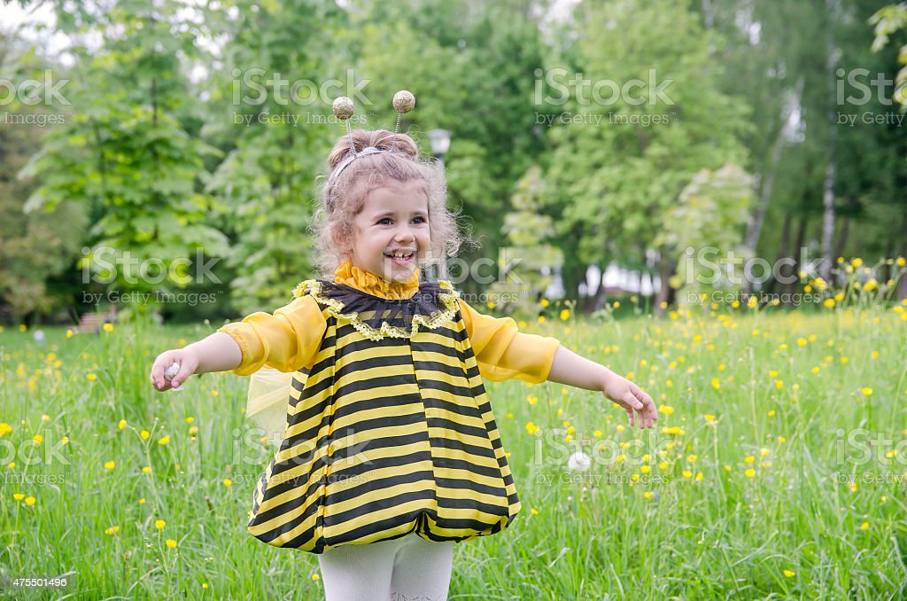 beautiful girl in a suit bee at park. Happy child stock photo