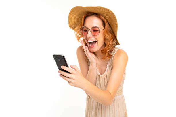 beautiful girl in a summer hat and sunglasses orders tickets on the phone on a white background stock photo