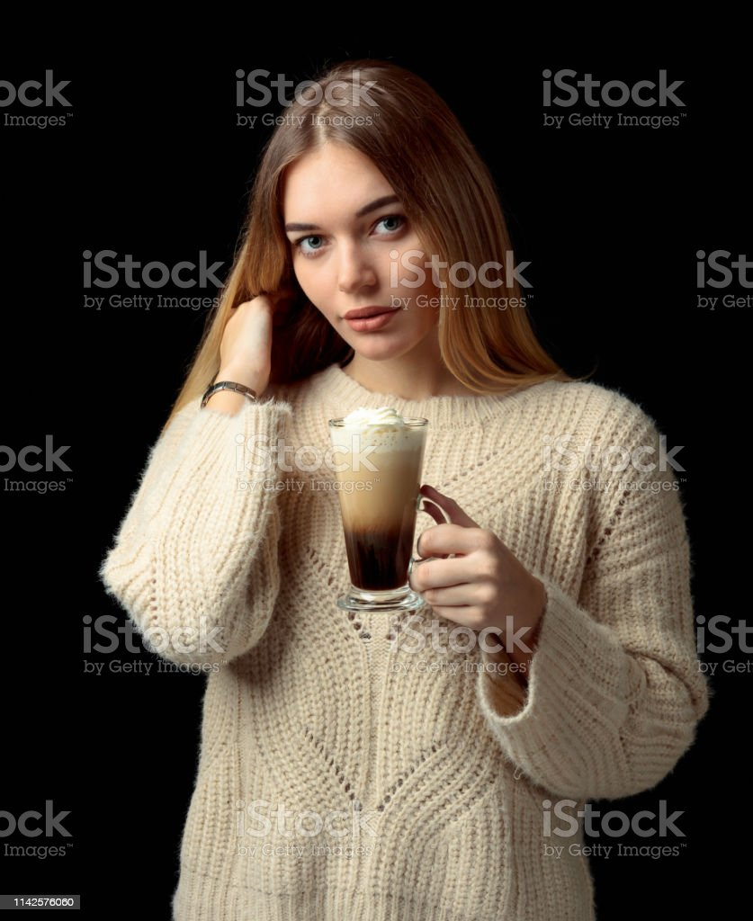 Beautiful girl in a sweater holding a mug of coffee cocktail with...