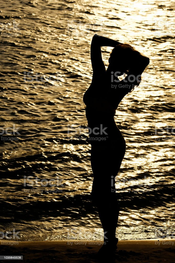 Beautiful girl in a swimsuit at sunset stock photo