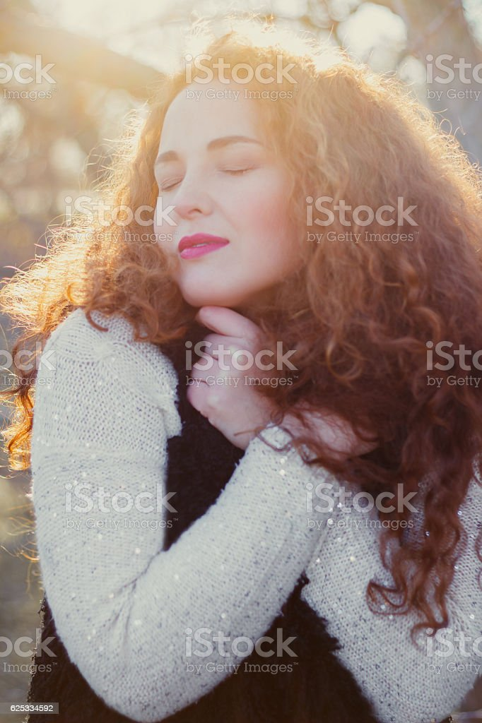 beautiful girl in a warm sweater and waistcoat, eyes closed stock photo