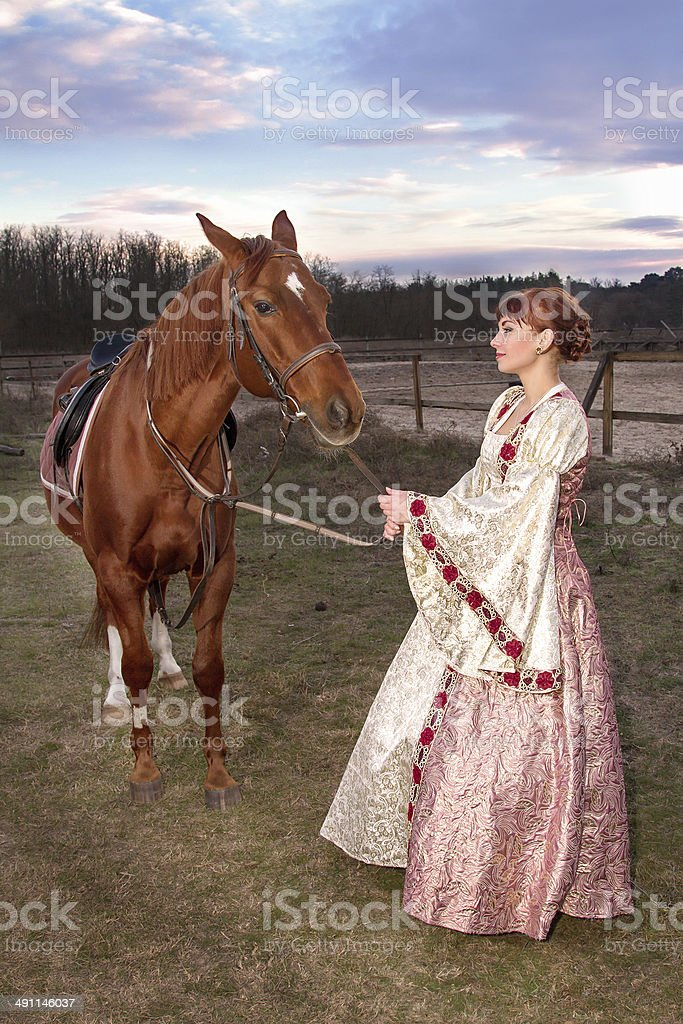 beautiful girl in antique dress next to a horse stock photo