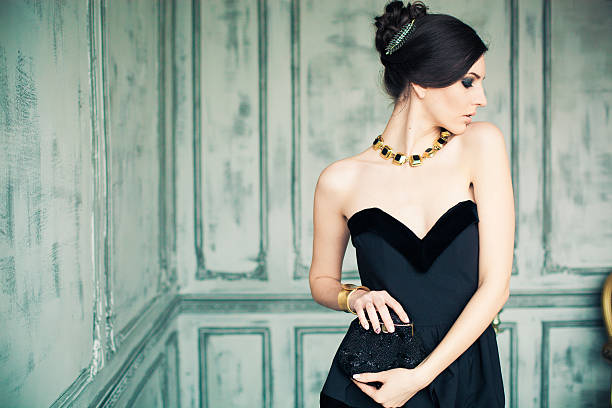 beautiful girl in black dress posing like diva - promi schmuck stock-fotos und bilder