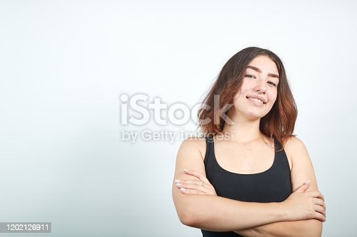 young beautiful brunette girl in black tank top over isolated white background happy face smiling with crossed arms looking at the camera. Positive person.