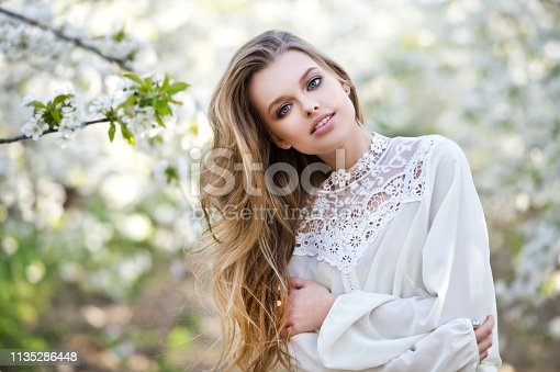 Beautiful girl in blossom cherry garden. Makeup. Beauty and fashion.