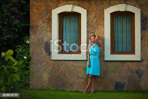 946294510 istock photo Beautiful girl in blue dress near the wall 528929791