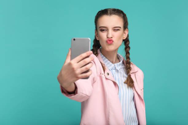 mooi meisje in casual of hipster stijl, pigtail kapsel, permanent, holding van mobiele smartphone en doen selfie of videobellen met kiss - selfie girl stockfoto's en -beelden