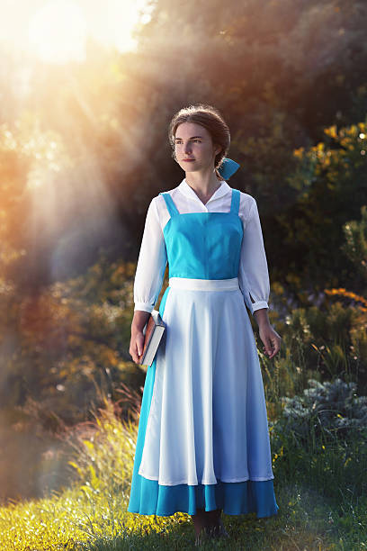 """beautiful girl in cosplay Belle beautiful girl in cosplay Belle of the animated film """"Beauty and the Beast"""" in the sun sun shining through dresses stock pictures, royalty-free photos & images"""