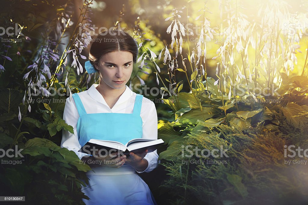 beautiful girl in cosplay Belle reading a book stock photo