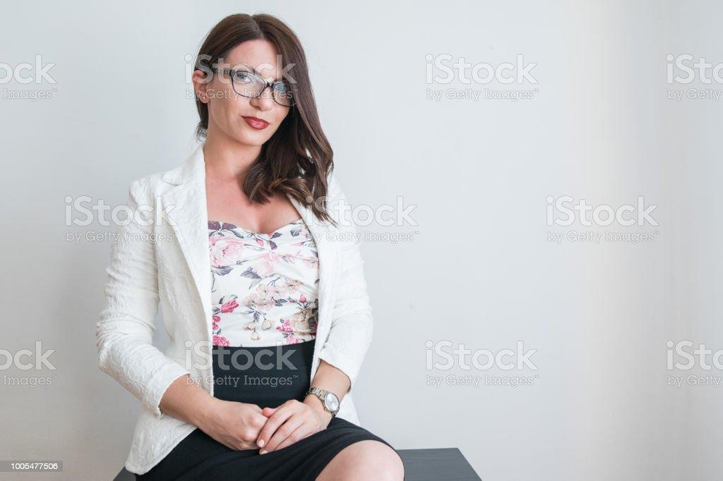 25ec4de87 hermosa chica en ropa elegante se sienta frente a una pared blanca foto de  stock libre